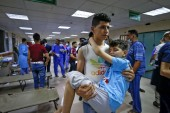 A young Palestinian man carries a boy, injured in Israeli air strikes, inside a hospital in Gaza City [Anas Baba/AFP]