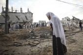 A Palestinian woman looks at destroyed buildings in Gaza on Thursday , the first day of the Eid al-Fitr holiday, which marks the end of the Muslim fasting month of Ramadan [Mahmud Hams/AFP]
