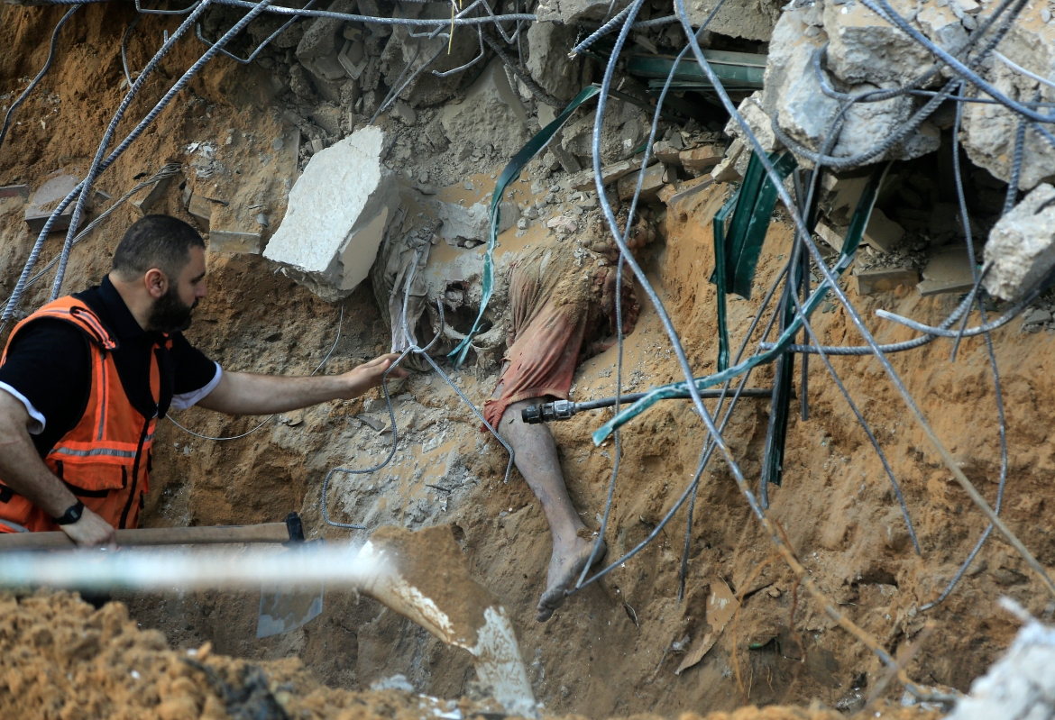 A Palestinian paramedic approaches a body buried in the rubble of a collapsed house belonging to the al-Tanani family in Beit Lahia in the northern Gaza Strip. [Qusay Dawud/AFP]