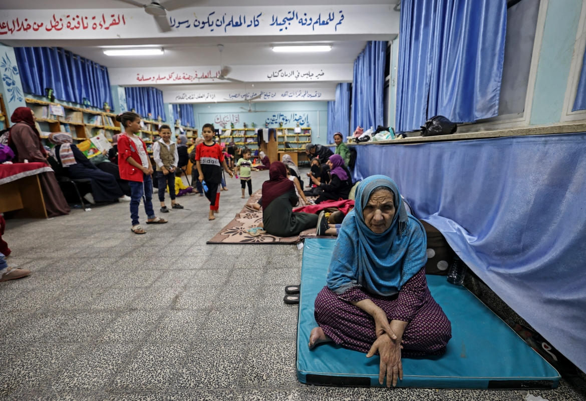 Palestinian families take shelter at a UN school in Gaza City after fleeing their homes in the town of Beit Lahia. [Mahmud Hams/AFP]