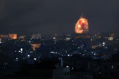 An explosion lights the sky following an Israeli air strike on Beit Lahia in the northern Gaza Strip early on Friday [Mohammed Abed/AFP]