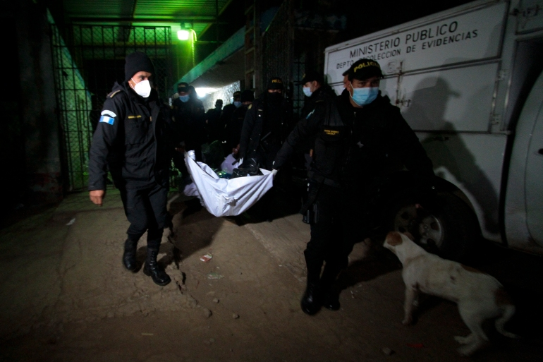 Police officers transport the corpse of an inmate after a 'riot' at the Cantel men's prison in Quetzaltenango in western Guatemala. [File: Alexis Morales/AFP]