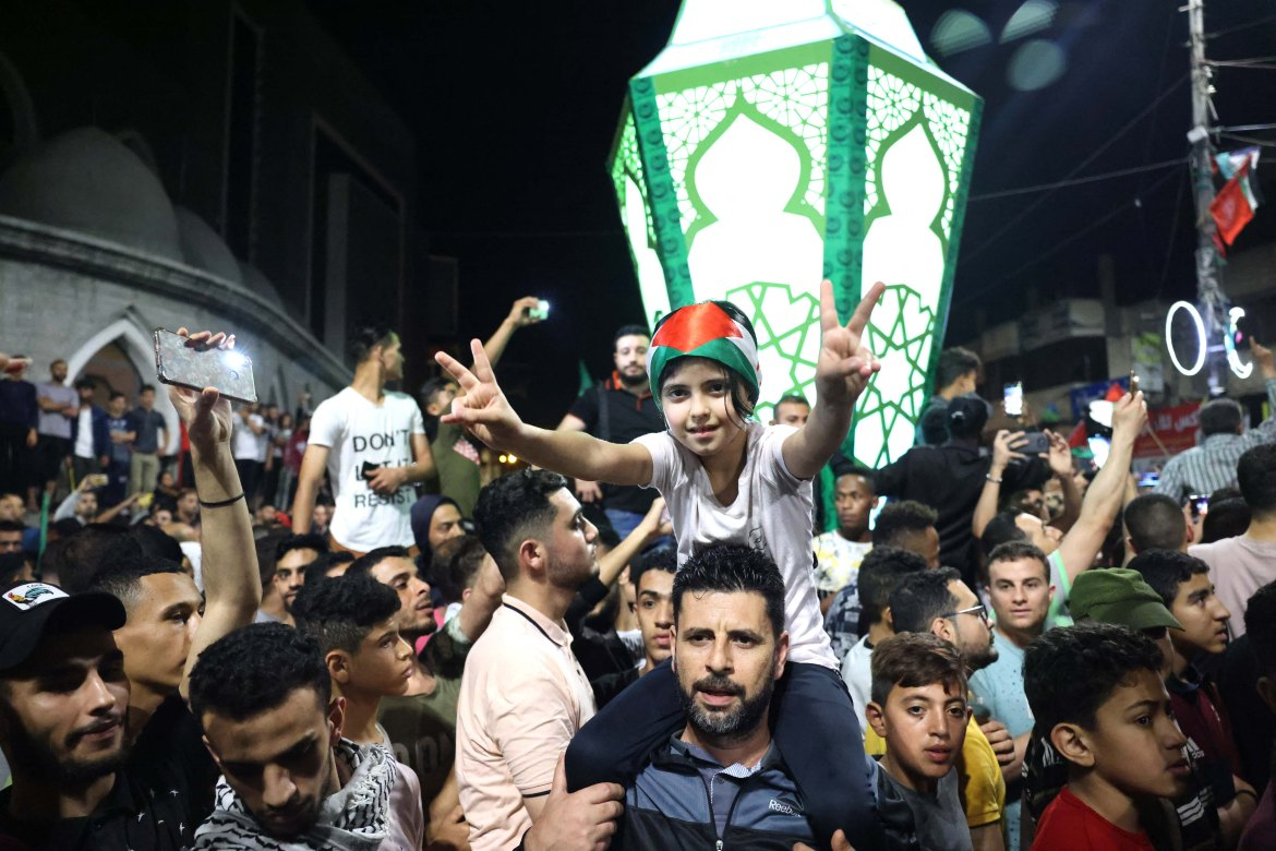 """Al Jazeera's Youmna al-Sayed, reporting from Gaza City, said Palestinians began celebrating as soon as the ceasefire came into effect. """"They started cheering and chanting 'God is Great,'"""" she said. """"And for them today, it's considered actually the first day of the Eid al-Fitr religious festival since the aggression started before the last day of Ramadan and they didn't really get to celebrate Eid."""" [Said Khatib/AFP]"""