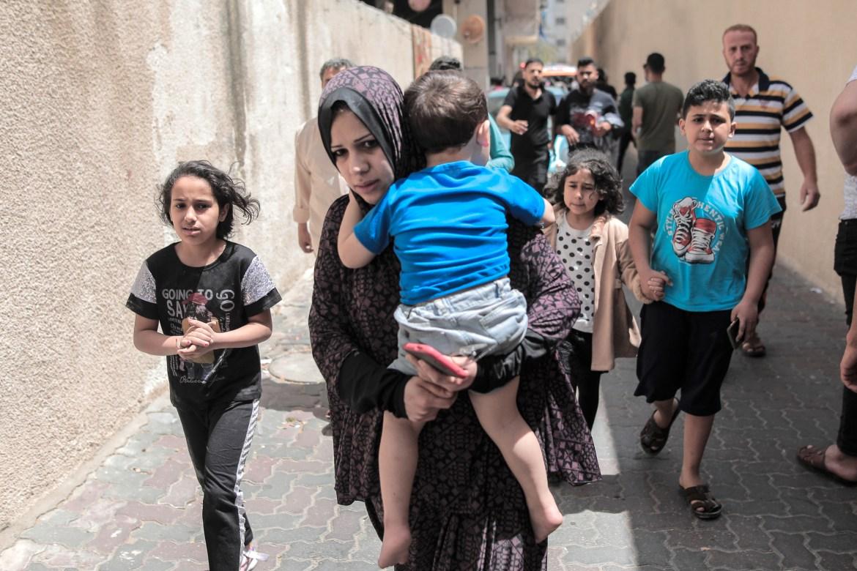 Seorang ibu menggendong anaknya di jalan setelah perumahan menara alJundi tempat mereka tinggal menjadi sasaran pesawat tak berawak Israel di Kota Gaza Hosam Salem / Al Jazeera