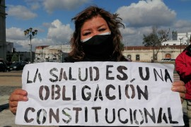 A protester holds a sign that reads 'Health Is A Constitutional Right' during a rally on May 8 in Guatemala City. [Sandra Cuffe/Al Jazeera]