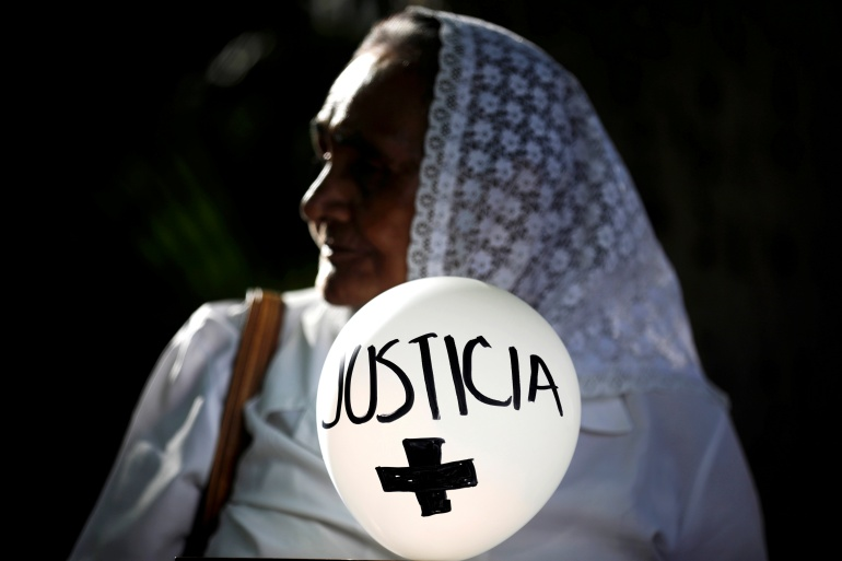 A woman holds a balloon that reads, 'Justice', during a protest against an amnesty bill to avoid prosecuting crimes committed during the civil war in San Salvador, El Salvador, on October 9, 2019 [File: Jose Cabezas/Reuters]