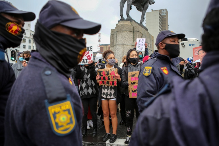 Police walk past demonstrators during a protest against gender-based violence outside the parliament in Cape Town in 2020 [File: Sumaya Hisham/Reuters]