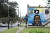 A mural depicts Ahmaud Arbery in Brunswick, Georgia, where he was fatally shot after being chased by three white men [File: Dustin Chambers/Reuters]