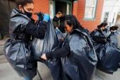 Staff from La Colaborativa, an aid group, use rubbish bags to pack up the belongings of a resident being evicted in Chelsea, Massachusetts, on March 26, 2021 [File: Brian Snyder/Reuters]