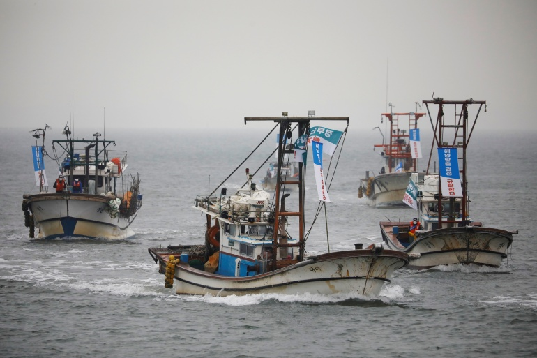 South Korean fishing boats take part in a marine protest, part of nationwide protests to demand Japan withdraw its decision to release contaminated water from its crippled Fukushima nuclear plant into the sea, at the sea off Incheon, South Korea, April 30, 2021. The banners read 'Condemning Japan's decision to release Fukushima water into the sea'. [Reuters/Kim Hong-Ji