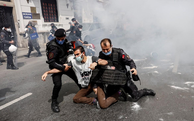 Petugas polisi anti huru hara menahan para demonstran saat mereka berusaha untuk menentang larangan dan berbaris di Lapangan Taksim Istanbul selama 'penutupan penuh' nasional yang diberlakukan untuk memperlambat laju virus korona Umit Bektas / Reuters