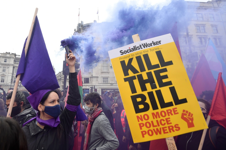 Seorang demonstran melepaskan asap berwarna selama protes 'Bunuh RUU' di Trafalgar Square, London melawan RUU yang diusulkan yang akan memberi polisi Inggris kekuatan ekstra untuk membatasi demonstrasi  Toby Melville / Reuters