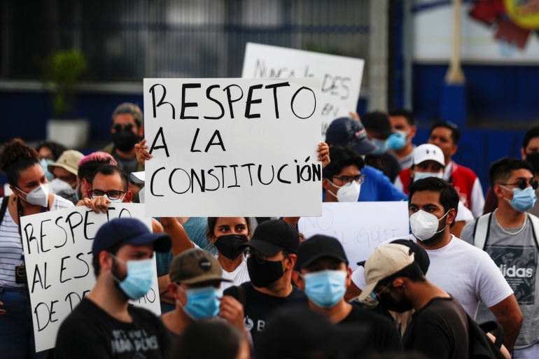 People hold signs reading 'Respect for the constitution', as they protest against the removal of Supreme Court judges and the attorney general by El Salvador's Congress, in San Salvador on May 2 [Jose Cabezas/Reuters]