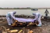 Men wearing protective suits place a white cloth over the body of their relative who died from COVID-19 before his cremation on the banks of Ganges River at Garhmukteshwar in Uttar Pradesh state [Danish Siddiqui/Reuters]