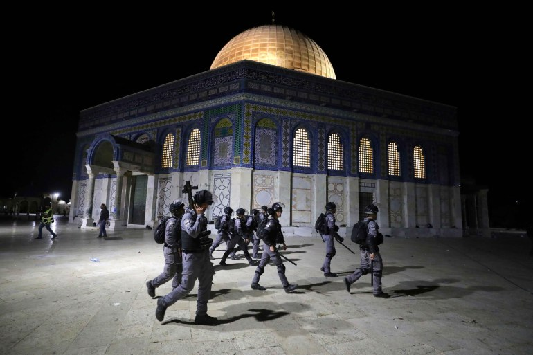 Israeli forces walk near the Dome of the Rock during a crackdown on Palestinian protests at Al-Aqsa compound against the possible forced expulsion of several Palestinian families from their homes in the Sheikh Jarrah neighbourhood of Jerusalem on May 7, 2021 [File: Ammar Awad/Rreuters]