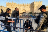 Israeli police officers tie barricades together at Damascus Gate in preparation for Laylat al-Qadr, or Night of Power, in Jerusalem's Old City [Stephen Farrell/Reuters]