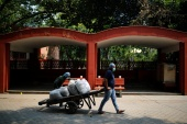 Volunteers carry bags containing unclaimed ashes of victims who died from COVID-19, on a cart at a crematorium in New Delhi [Adnan Abidi/Reuters]