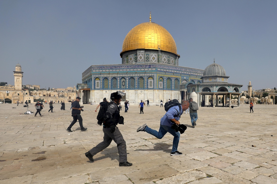 Israeli police chase a cameraman covering the raid on Palestinians at Al-Aqsa compound. [Ammar Awad/Reuters]