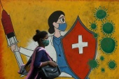 A woman walks past a graffito on a street amid the spread of the coronavirus disease in Mumbai [Francis Mascarenhas/Reuters]