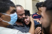 Relatives of a Palestinian who was killed by Israeli air raids launched on the Gaza Strip [Mohammed Salem/Reuters]