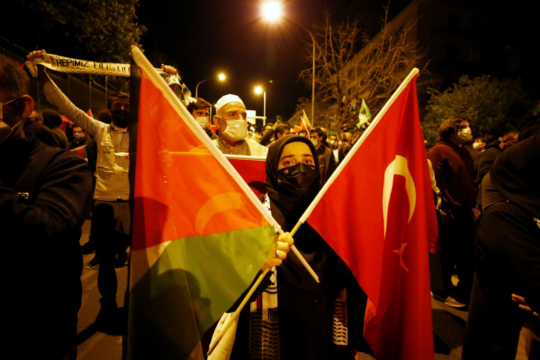 Demonstrators in Ankara carried Turkish and Palestinian flags. [Cagla Gurdogan/Reuters]