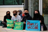 Protesters display banners against vaccine patents outside the AstraZeneca site in Cambridge, UK [Andrew Couldridge/Reuters]