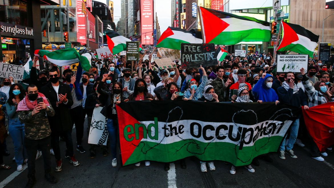 Demonstrators march on Times Square in New York City to express their solidarity with Palestinians. [Eduardo Munoz/Reuters]