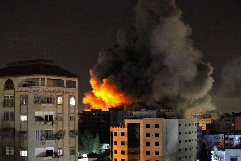 Smoke rises from a tower in Gaza after it was hit by Israeli air strikes early on Wednesday [Ibraheem Abu Mustafa/Reuters]