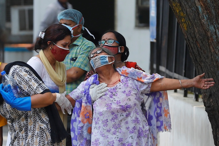 A woman mourns after seeing the body of her son who died due to COVID-19, outside a mortuary of a hospital in New Delhi [Adnan Abidi/Reuters]