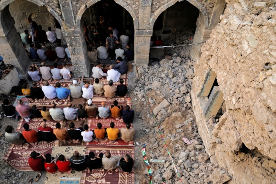 People attend Eid al-Fitr prayers marking the end of the holy fasting month of Ramadan, at al-Masfi mosque, which was damaged during the war against ISIL (ISIS) in Mosul, Iraq [Abdul Rashid/Reuters]