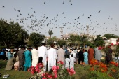 Pakistani Muslims gather to celebrate Eid al-Fitr prayers to mark the end of the holy fasting month of Ramadan, amid a coronavirus outbreak in Karachi. [Akhtar Soomro/Reuters]