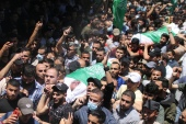 Palestinians attend the funeral of people who were killed in an Israeli air strike in Gaza City [Mohammed Salem/Reuters]