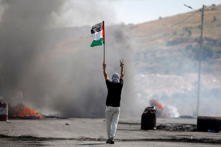 A demonstrator holding a Palestinian flag gestures during a protest, near Hawara checkpoint in the occupied West Bank, May 14, 2021 [File: Raneen Sawafta/Reuters]