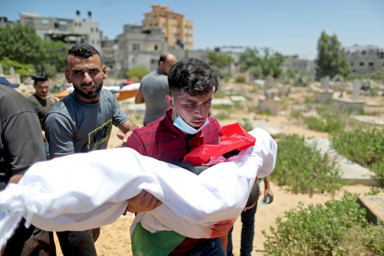 A man carries the body of a Palestinian child from Al-Hadidi family, who was killed amid a flare-up of Israeli-Palestinian violence, during their funeral at a cemetery in the northern Gaza Strip May 15, 2021. REUTERS/Suhaib Salem