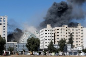 Israeli air strikes flatten the 13-storey al-Jalaa Tower where Al Jazeera and AP offices were [Mohammed Salem/Reuters]
