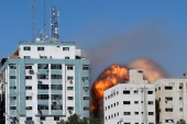 Gaza tower housing AP, Al Jazeera is seen during a missile attack in Gaza city, May 15, 2021 [Mohammed Salem/Reuters]