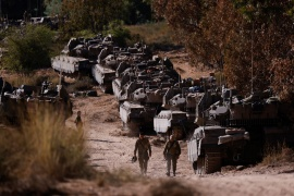 Israeli soldiers walk next to tanks near the border between Israel and the Gaza Strip, on its Israeli side [Amir Cohen/Reuters]