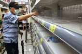 A man takes instant noodles from a near-empty shelf as customers rush to buy their groceries, after the government advised people to reduce leaving their homes and limit gatherings due to an increasing number of locally transmitted COVID-19 infections, in Taipei, Taiwan, May 16, 2021 [Ann Wan/ Reuters]