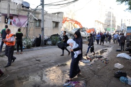 People walk past debris in a street at the site of Israeli air strikes, in Gaza City on May [Mohammed Salem/Reuters]