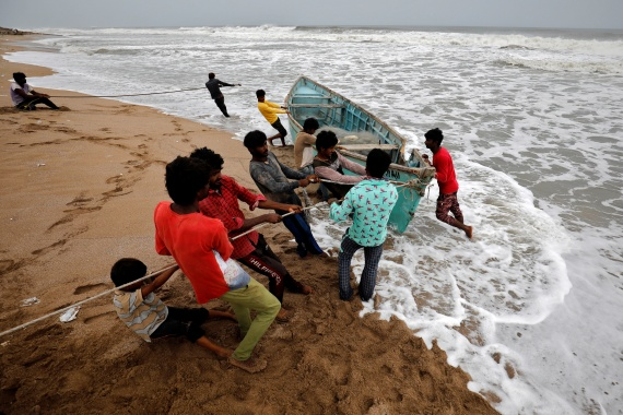 People move a fishing boat to a safer place along the shore ahead of Cyclone Tauktae in Veraval in the western state of Gujarat [Amit Dave/Reuters]