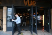Asa Brennan, general manager of Vue Cinema in Leicester Square, opens the doors as COVID restrictions continue to ease in London, Britain [Toby Melville/Reuters]