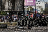 Palestinians stand behind tires during a protest near Hawara checkpoint near Nablus in the Israeli-occupied West Bank [Raneen Sawafta/REUTERS]