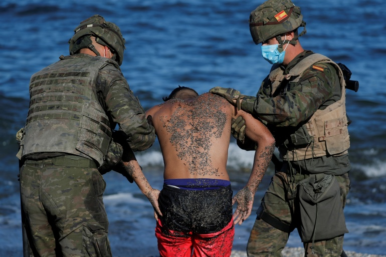 More than 8,000 people entered Ceuta on Monday and Tuesday after swimming around a breakwater that extends into the Mediterranean Sea or climbing over the border fence that separates the Spanish territory from Morocco [Jon Nazca/Reuters]