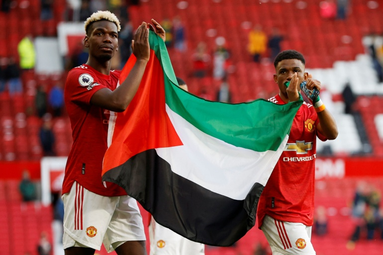 Manchester United's Paul Pogba (L) and Amad Diallo applaud fans while holding a Palestinian flag [Phil Noble/Reuters]
