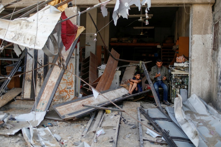 Palestinians sit amidst the damage in the aftermath of Israeli air strikes in Gaza [Mohammed Salem/AP]