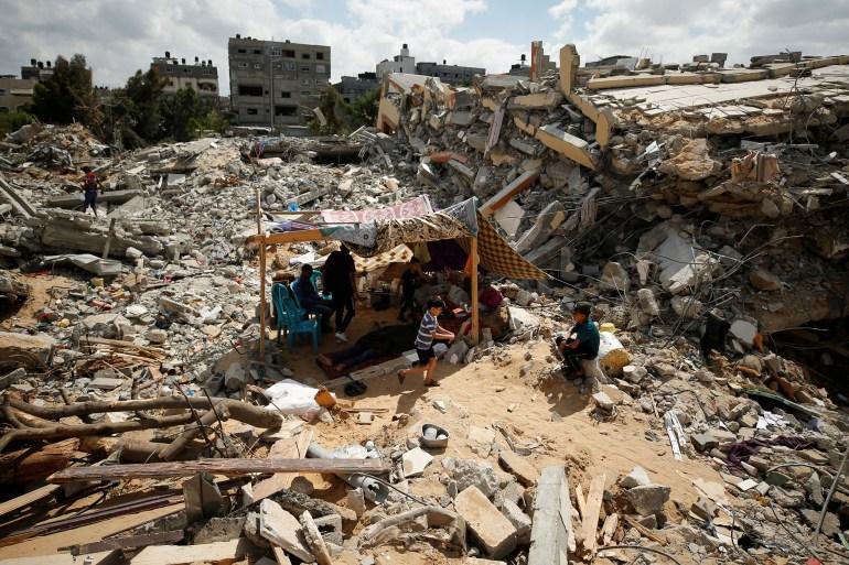 Warga Palestina duduk di tenda darurat di tengah puingpuing rumah mereka yang dihancurkan oleh serangan udara Israel Mohammed Salem / Reuters