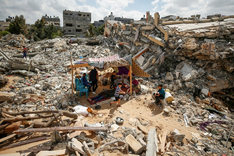 Palestinians sit in a makeshift tent amid the rubble of their houses on May 23, 2021 [Mohammed Salem/Reuters]