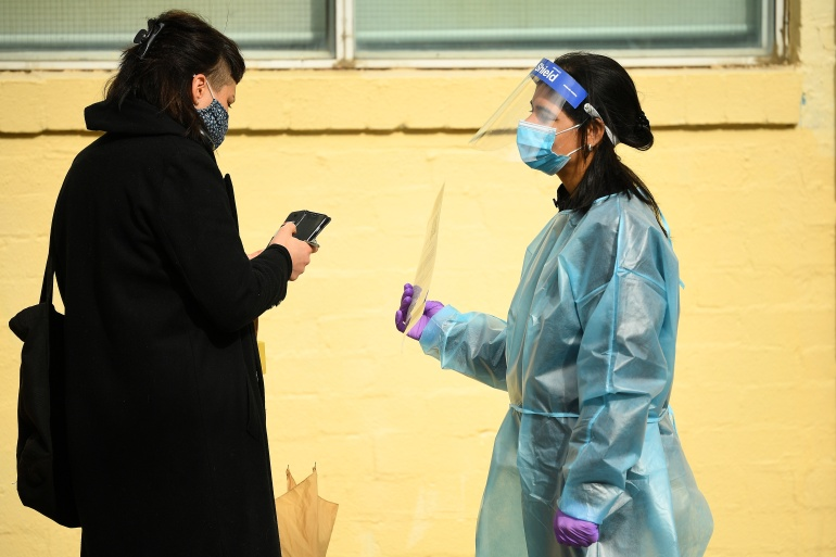 A healthcare worker speaks with a member of the public waiting to get tested for COVID-19 [James Ross/AAP Image via Reuters]
