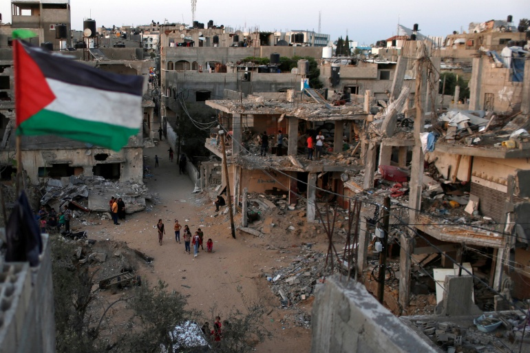 A Palestinian flag flies next to the ruins of houses destroyed by Israeli air strikes during the recent Israeli assault on Gaza on May 25, 2021. [Reuters/Mohammed Salem]