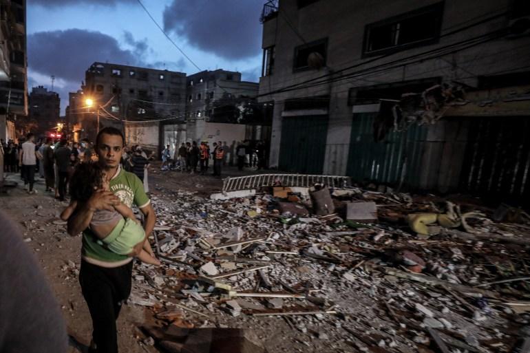 A man holding his child flees the carnage after Israeli warplanes attacked the Gaza Strip [Ali Jadallah/Anadolu]